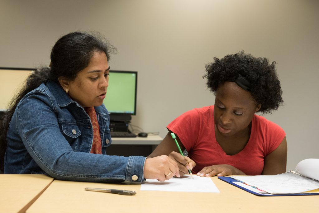 An adult learner works with a volunteer tutor at the Library. © steven e gross17919 Waukegan Public Library